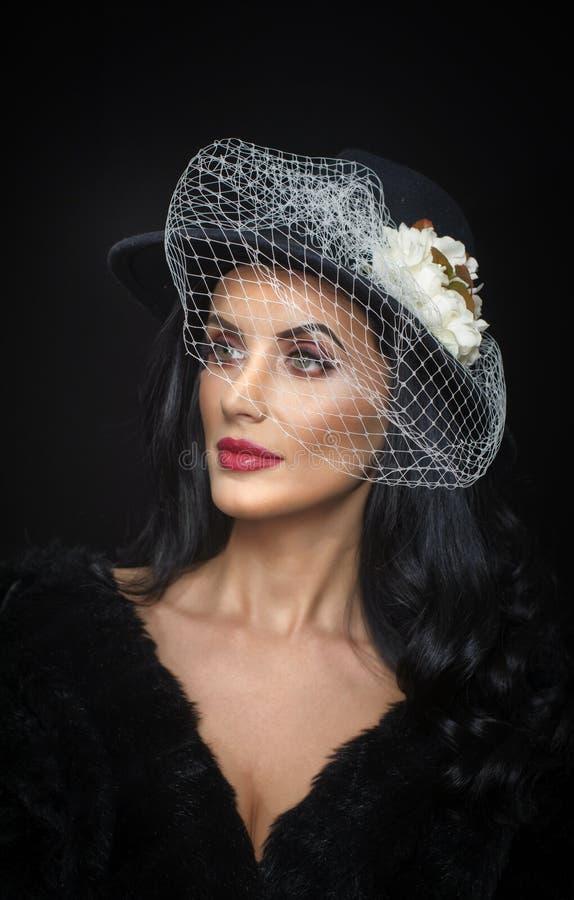 O penteado e compõe - o retrato bonito da arte da jovem mulher Morena bonito com arranjo branco do véu e de flor, tiro do estúdio fotografia de stock