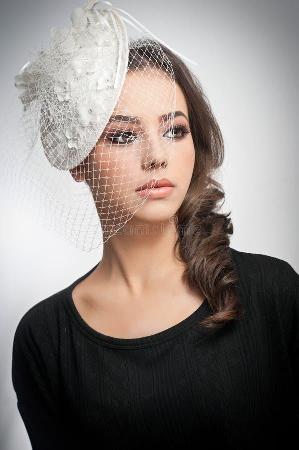 O penteado e compõe - o retrato bonito da arte da moça Morena bonito com tampão e o véu brancos, tiro do estúdio Fêmea atrativa foto de stock royalty free