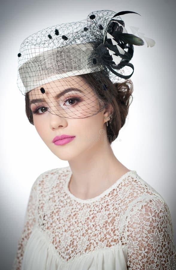 O penteado e compõe - o retrato bonito da arte da moça Morena bonito com tampão e o véu brancos, tiro do estúdio Menina atrativa imagens de stock royalty free