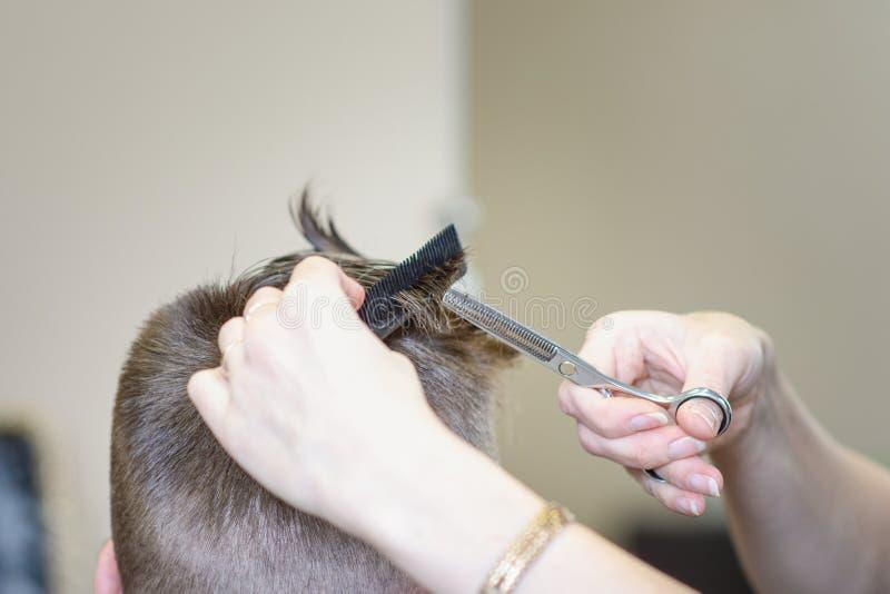 O penteado e o corte de cabelo dos homens bonitos em um cabeleireiro ou no cabeleireiro imagem de stock