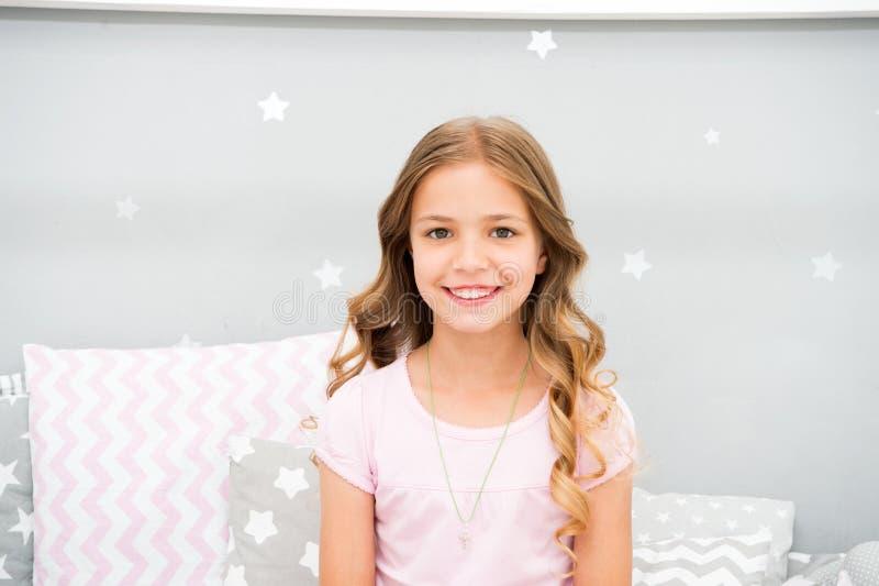 O penteado encaracolado perfeito da criança olha bonito Usa o condicionador ou a máscara com óleos orgânicos para manter o cabelo imagem de stock royalty free