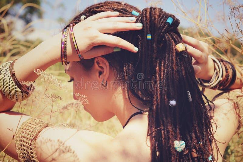O penteado vestindo dos dreadlocks da jovem mulher bonita recolheu em um rabo de cavalo e decorou grânulos sortidos foto de stock