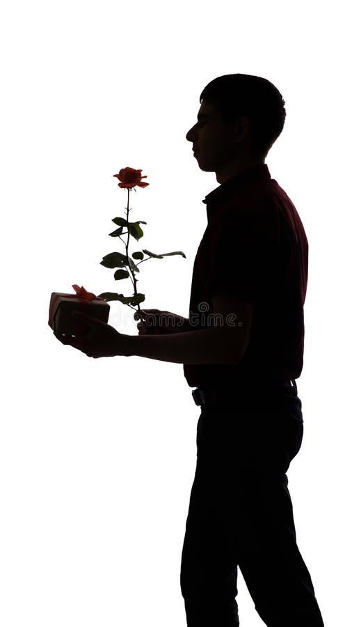 O perfil da silhueta de um homem com uma caixa de presente e uma flor cor-de-rosa para seu amado, o indivíduo felicita no fundo i imagem de stock royalty free