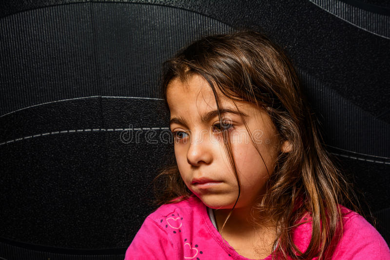 O perfil de uma menina triste está sentando-se no canto da sala imagem de stock