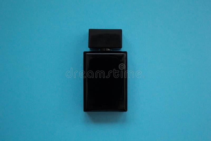 O perfume dos homens na garrafa preta bonita em um fundo azul imagem de stock