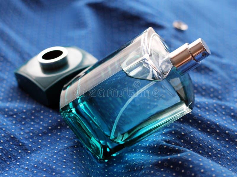 O perfume verde dos homens na garrafa bonita na matéria têxtil azul imagem de stock royalty free