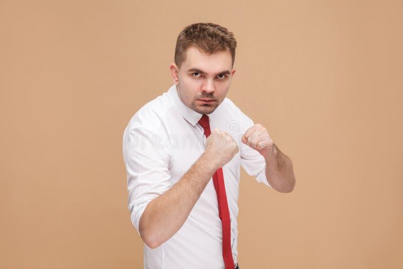 O perigo e o homem de negócios forte que mostram o sinal do encaixotamento e aprontam-se a f foto de stock
