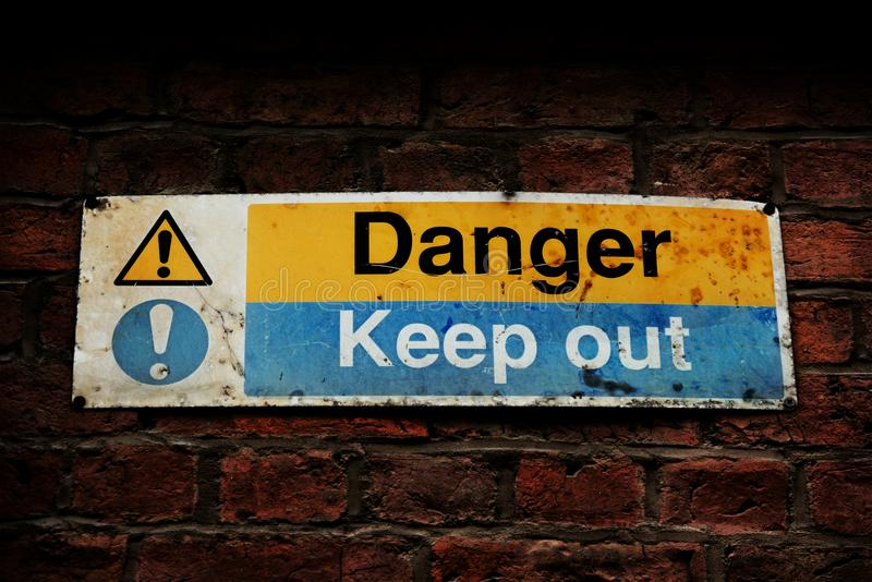 O perigo, mantém para fora o sinal em uma parede de tijolo imagens de stock royalty free