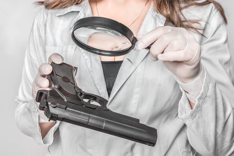 O perito da criminologia que olha a pistola e recolhe a evid?ncia imagens de stock royalty free