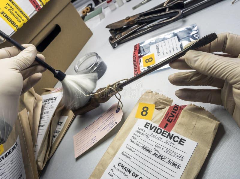 O perito da polícia revela traços em uma chave de fenda da cena de um crime foto de stock