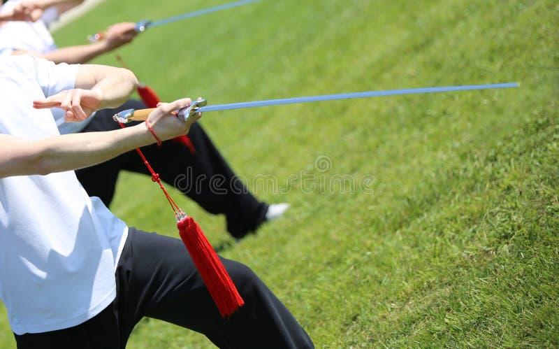 O perito do atleta das artes marciais de Tai Chi faz movimentos com espada imagens de stock