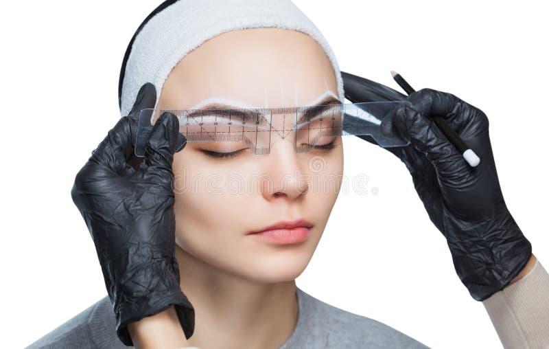 O Permanent compensa pelas sobrancelhas da mulher bonita com as testas grossas no salão de beleza imagem de stock
