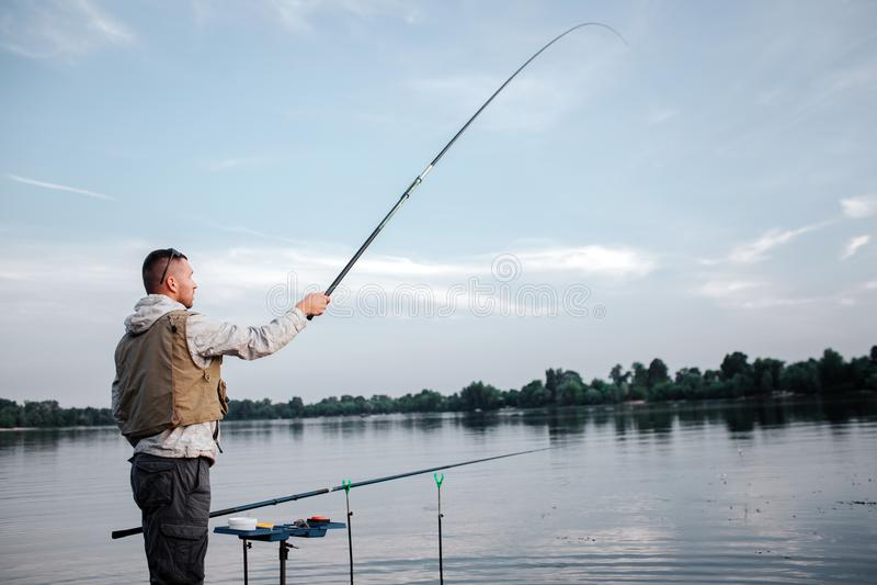 O pescador é haste de mosca próxima ereta do watr e da terra arrendada com assistente Tem-no acima realmente altamente O homem ol imagem de stock royalty free