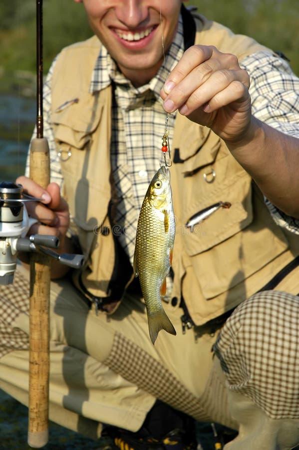 O pescador apenas travou um peixe fotografia de stock royalty free