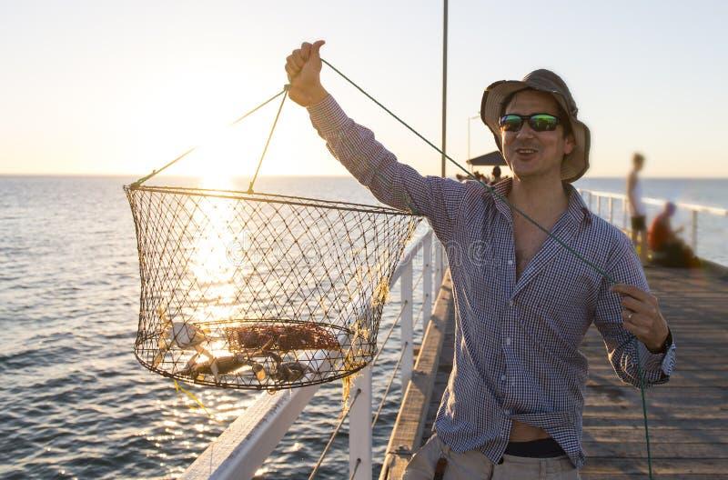 O pescador atrativo orgulhoso que mostram peixes e os caranguejos as captações da rede da cesta que sorriem no mar entram o por d foto de stock