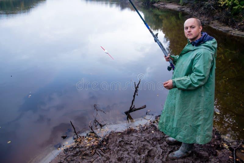 O pescador com vara de pesca pesca O canal do rio Nadym imagem de stock royalty free