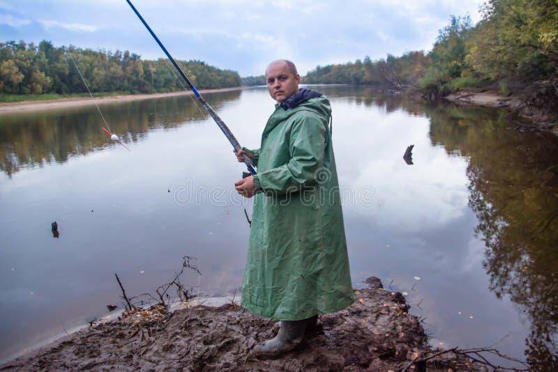 O pescador com a vara de pesca que está na lama pesca O canal do rio Nadym fotos de stock royalty free
