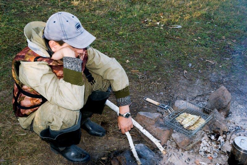 O pescador cozinha o alimento em um incêndio foto de stock