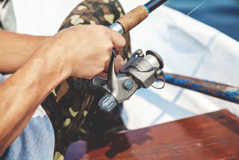 O pescador das mãos que guarda a vara de pesca e o punho do carretel é girado foto de stock