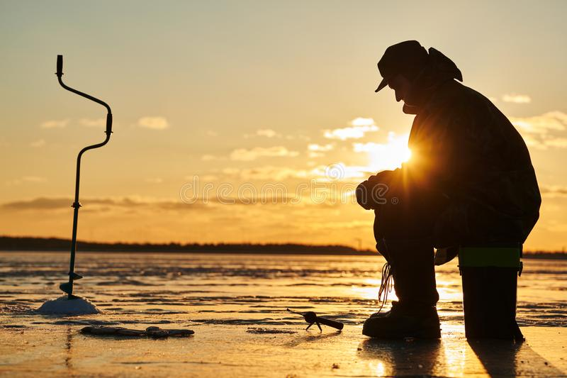 O pescador do pescador na pesca do inverno do gelo Por do sol imagem de stock royalty free