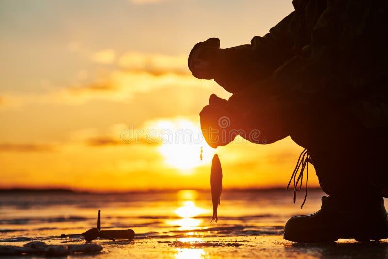 O pescador do pescador na pesca do inverno do gelo Por do sol fotos de stock