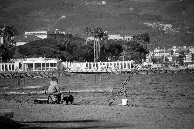 O pescador e é cão imagens de stock