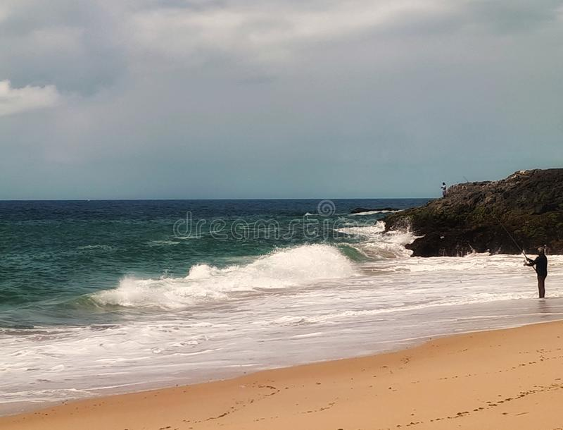 O pescador e o mar áspero fotos de stock royalty free
