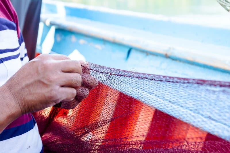 O pescador está fixando a rede dos peixes imagens de stock royalty free