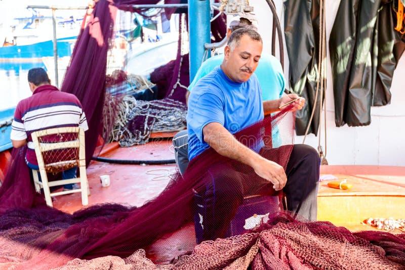 O pescador está fixando a rede dos peixes imagens de stock