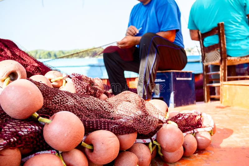 O pescador está fixando a rede dos peixes imagem de stock