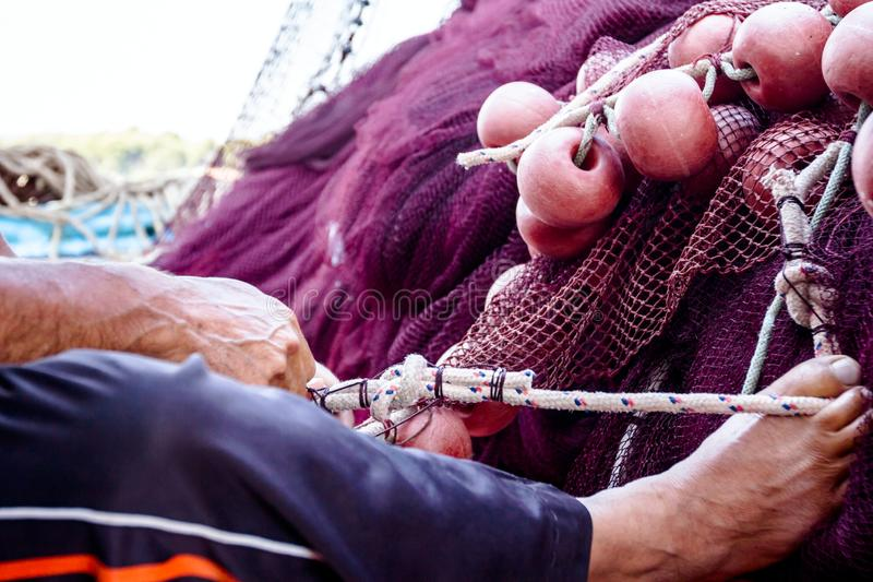 O pescador está fixando a tração da rede dos peixes com seu pé fotografia de stock