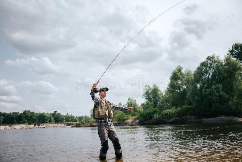O pescador está na haste de mosca rasa e guardando acima em umas mão e porção da colher na outra O homem está olhando acima Ele foto de stock royalty free
