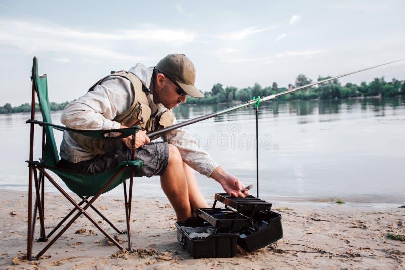 O pescador está sentando-se na cadeira de dobradura e está inclinando-se para a frente à caixa plástica preta aberta As posses do foto de stock