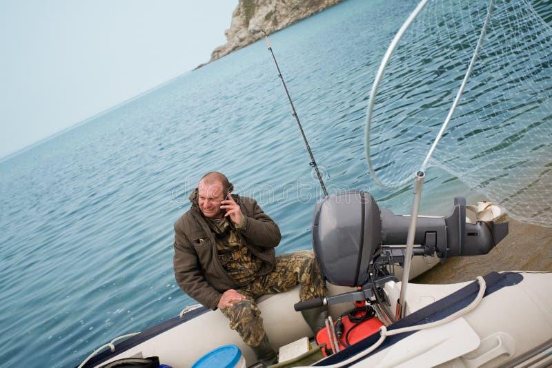 O pescador estava falando em seu móbil fotos de stock