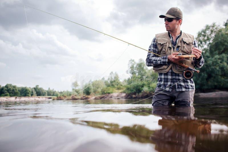 O pescador fresco está na água e olha direto E As posses do indivíduo voam a haste e a caixa de madeira de artificial fotos de stock royalty free