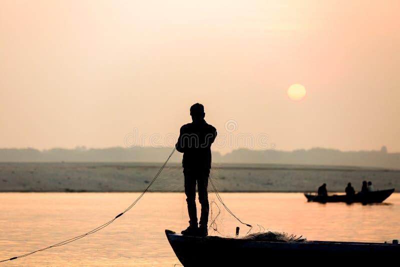 O pescador joga a rede no nascer do sol em Ganges River, Varanasi foto de stock royalty free