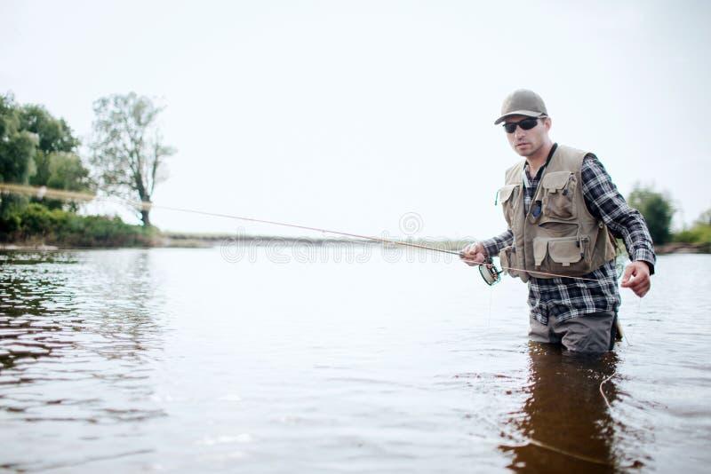 O pescador na roupa da proteção stnading na água e na pesca Guarda a haste dos peixes em uma mão e puxa a colher com foto de stock