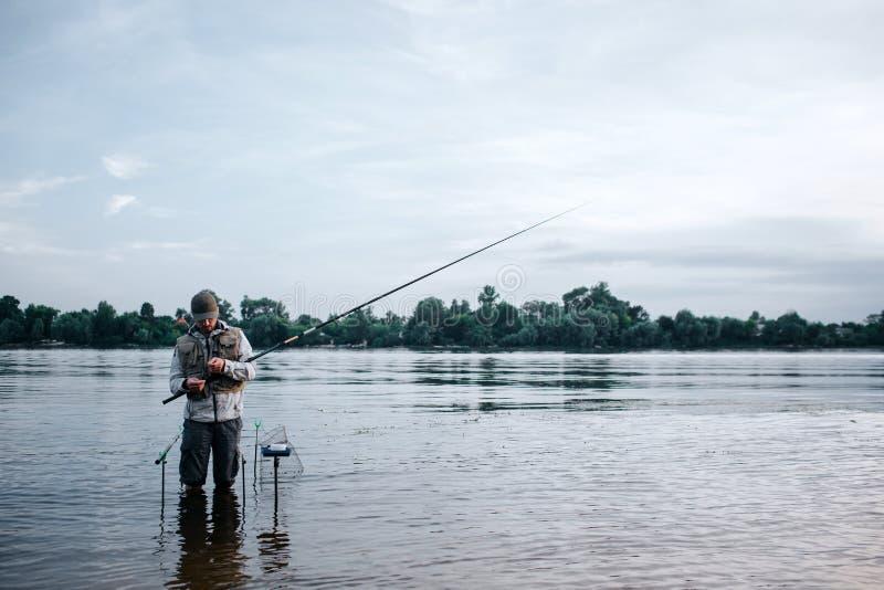 O pescador novo é barefeet ereto na água e na haste de mosca da terra arrendada Olha-o O indivíduo está trabalhando com colher e  fotografia de stock