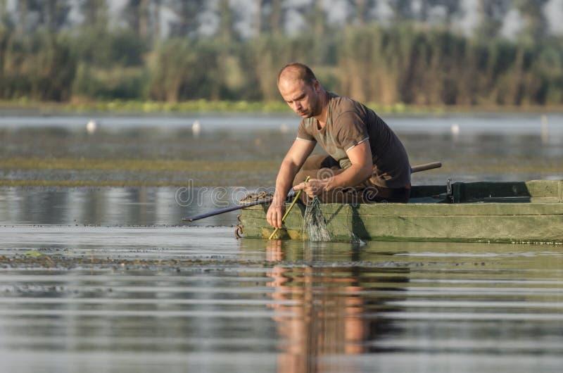 O pescador puxa a rede fotos de stock