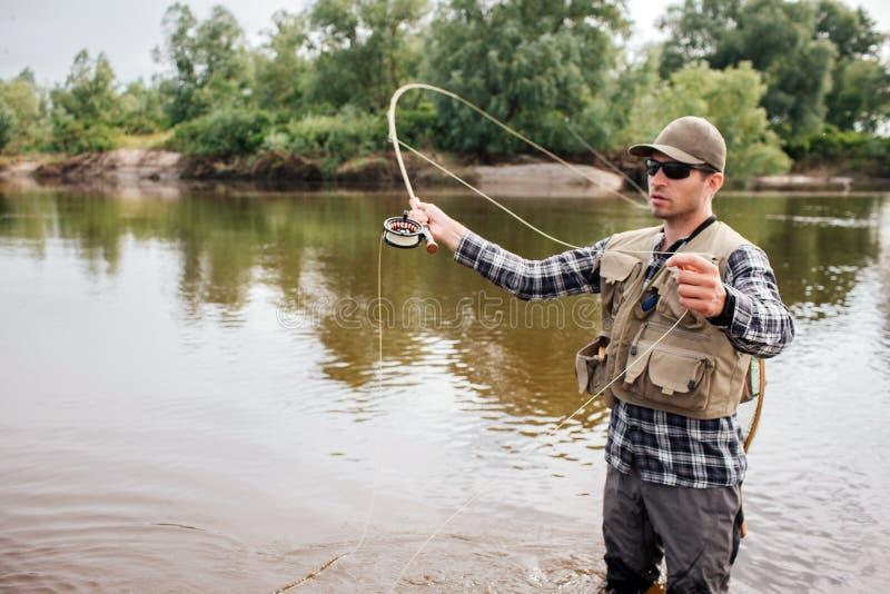 O pescador sério está em raso uma ondulação com pesca com mosca Igualmente tem uma colher na outra mão O indivíduo está olhando a foto de stock