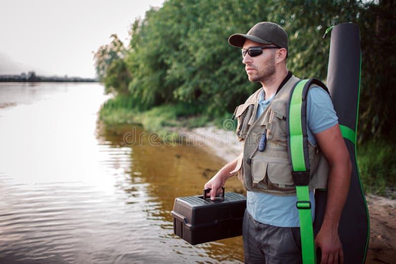 O pescador sério está estando em raso e está olhando direto Guarda a caixa negra plástica em umas mão e tampa fotos de stock