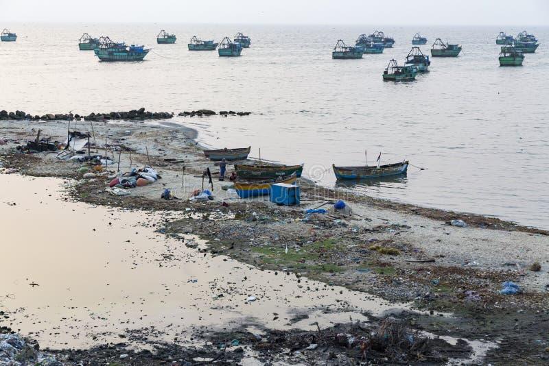 O pescador tradicional local dos pobres não identificados está vivendo na praia no meio do lixo e as vacas e as cabras, sob barra fotografia de stock royalty free