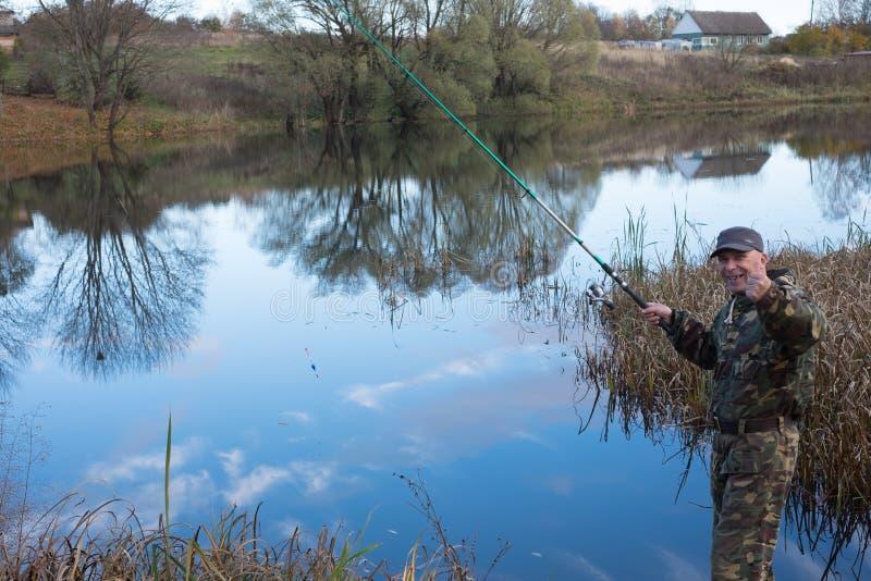 O pescador trava peixes no lago fotos de stock royalty free