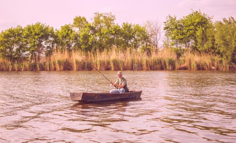O pescador trava um peixe - pesca do homem no rio foto de stock royalty free