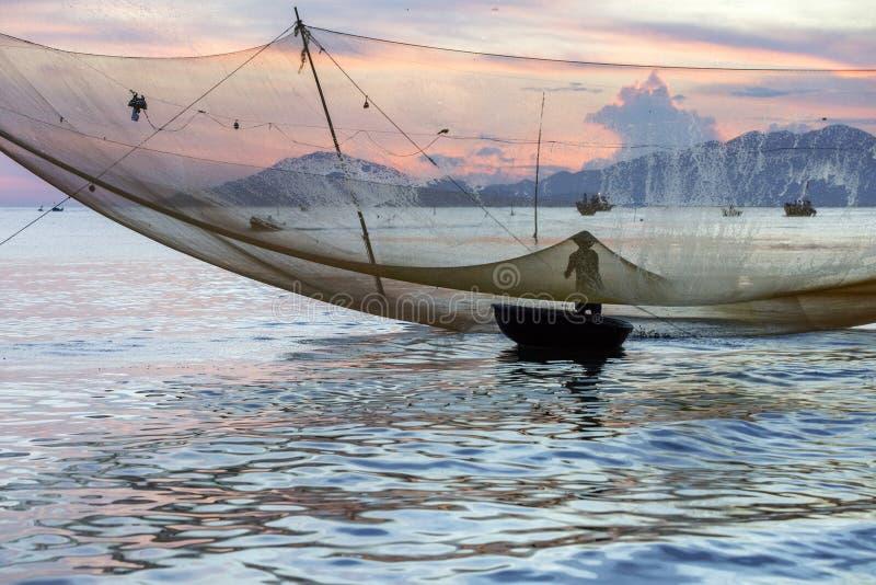 O pescador verifica suas redes no amanhecer no rio em Hoian, Vietname fotografia de stock