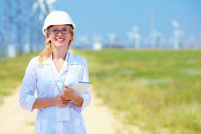 O pesquisador fêmea novo analisa readouts na central elétrica de energias eólicas fotografia de stock royalty free