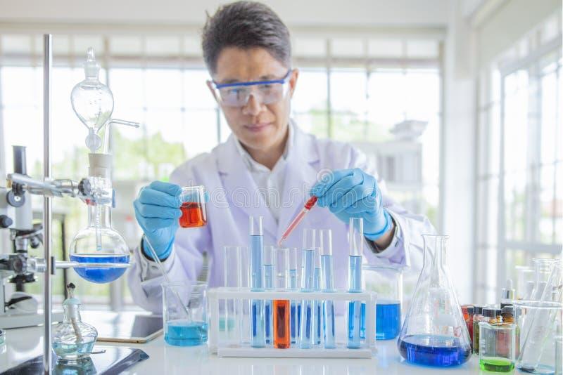 O pesquisador que trabalha em laboratary, cientistas está experimentando com os produtos químicos do gotejamento nos tubos de ens fotos de stock royalty free