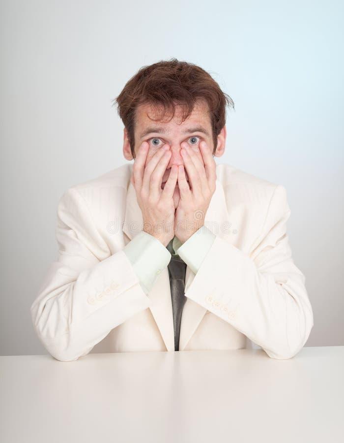 O pessoa doloroso novo no terno branco senta-se na tabela foto de stock royalty free