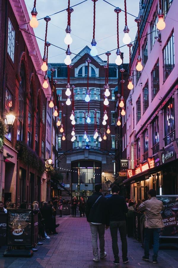 O pessoa que anda sob a ampola ilumina-se na rua de Carnaby, Londres, Reino Unido imagens de stock royalty free