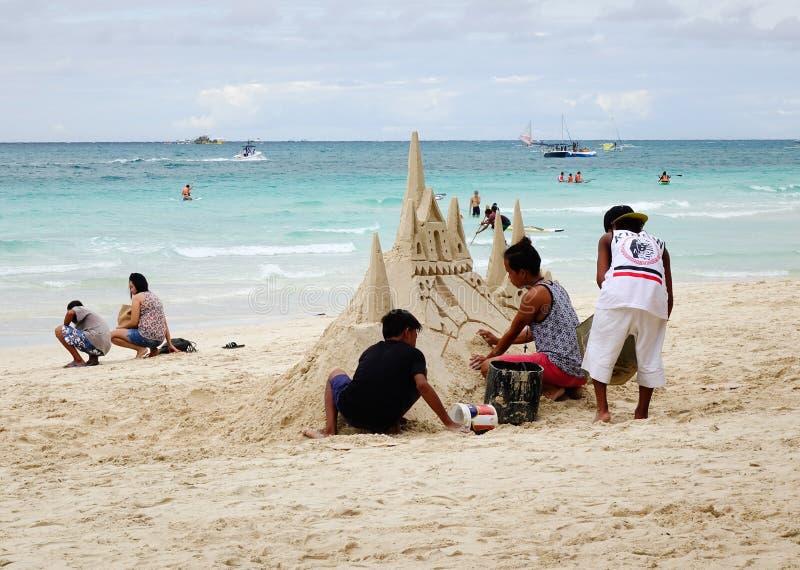 O pessoa que faz a areia fortifica na praia em Boracay, Filipinas fotos de stock